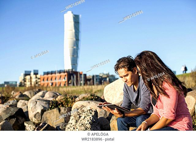 Young couple using digital tablet on rocks with Turning Torso skyscraper in background