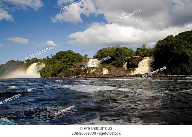 Canaima Village three waterfalls that feed into Canaima lake with blue sky and white clouds