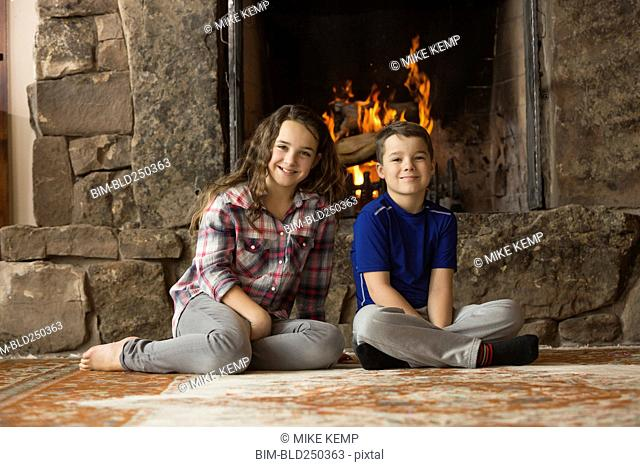 Smiling Caucasian brother and sister sitting on floor near fireplace