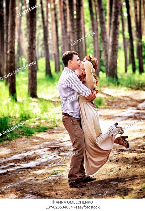 Loving couple having fun in the forest, kissing and whirling around themselves, happy bride and groom enjoying wedding day