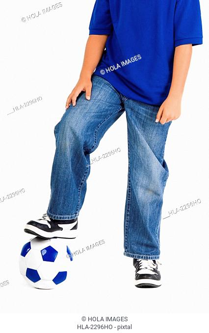 Close-up of a boy standing with his foot on a soccer ball