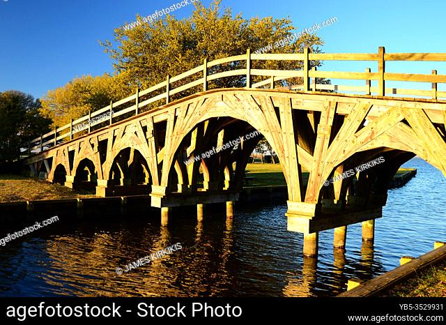 A beautiful wooden pedestrian bridge crosses a small creek in a park in the Outer Banks of North Carolina