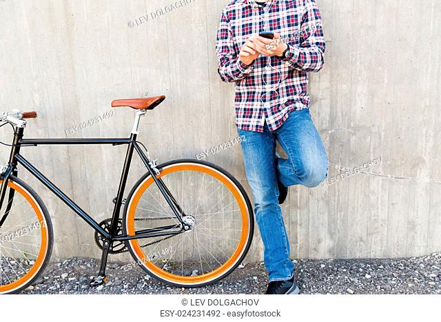 people, style, technology, leisure and lifestyle - close up of young hipster man in earphones with smartphone and fixed gear bike listening to music on city...