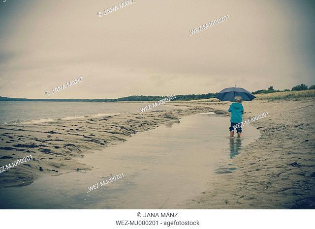 Germany, Mecklenburg Western Pomerania, Boy with umbrella in rain at baltic sea
