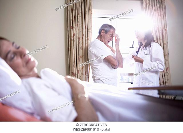 Doctor consoling senior man in hospital