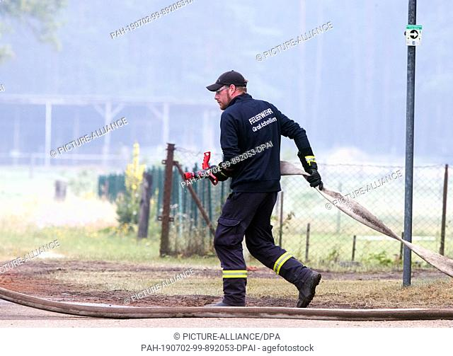 02 July 2019, Mecklenburg-Western Pomerania, Alt Jabel: Firefighters distribute water in the evacuated place and try to keep the paths wet