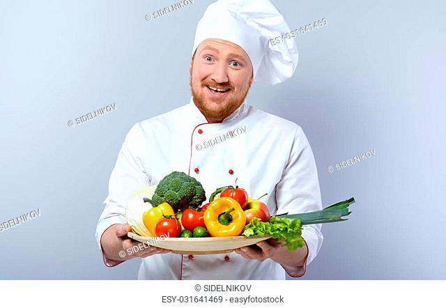 Portrait of positive young male chef in white uniform. Head-cook cheerfully smiling, looking at camera and proposing big plate of fresh vegetables