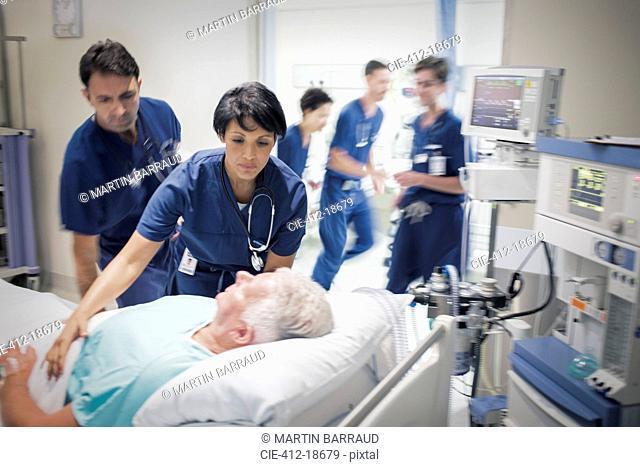 Two doctors preparing elderly patient before medical procedure