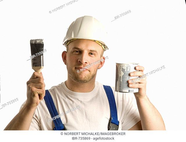 Construction worker holding a can of paint and a paintbrush