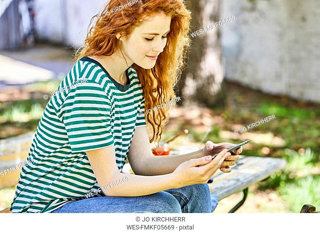 Smiling redheaded young woman sitting on bench in the garden looking at cell phone