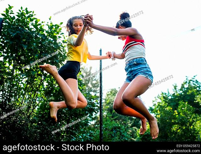 Low angle view of cheerful young teenager girls friends outdoors in garden, jumping on trampoline