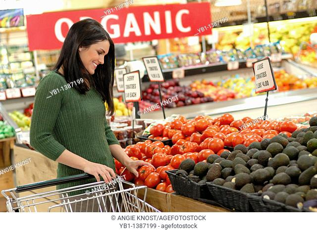 Attractive woman grocery shopping, in the produce section  An 'Organic' sign in the background shows she is shopping for organic produce