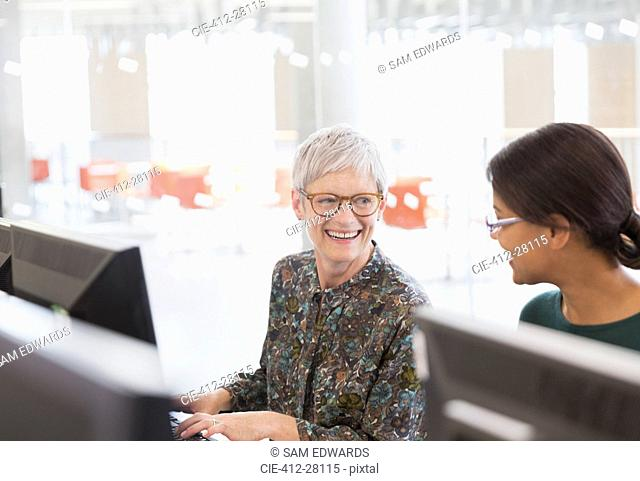 Smiling women talking at computers in adult education classroom