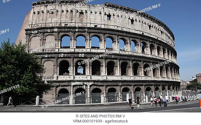 Daylight, Exterior, PAN on the walls of the Coliseum on the southern side, tourists walking around the Coliseum. This is an elliptical amphitheater in the...