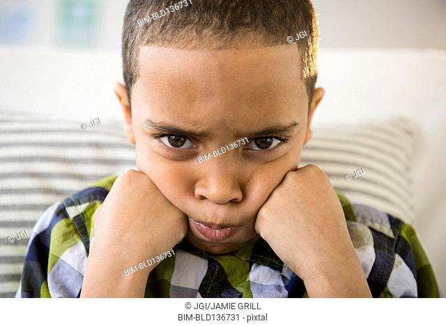 Mixed race boy pouting on sofa
