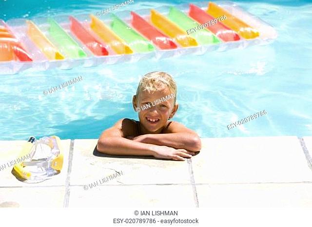 Boy (7-9) in swimming pool, smiling, portrait