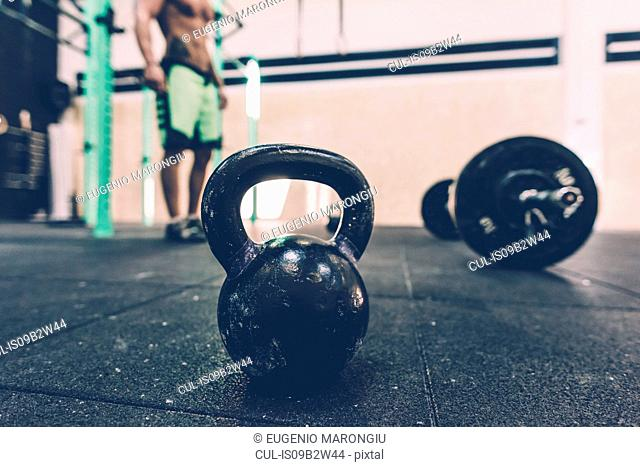 Kettlebell and barbell on floor of cross training gym