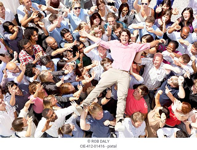 Portrait of enthusiastic man crowd surfing