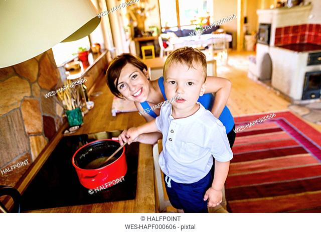 Little boy helping his pregnant mother to cook, stirring in pot