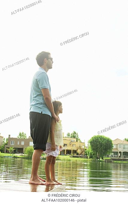 Father and daughter standing together at end of lake pier looking at view