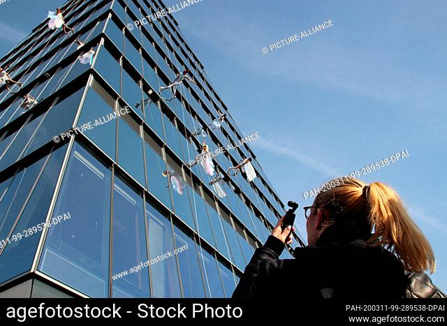 11 March 2020, US, New York: A woman photographs the performers on the house wall during the official opening ceremony of the triangular viewing platform Edge