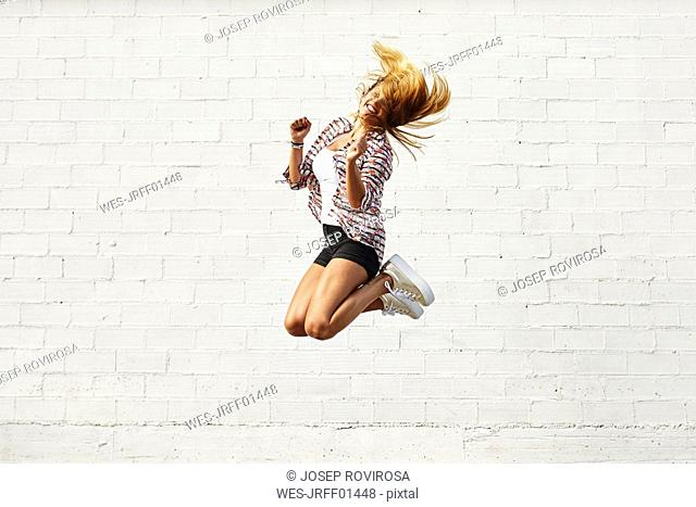 Happy young woman jumping mid-air in front of white wall