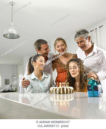 Family sitting around a birthday cake