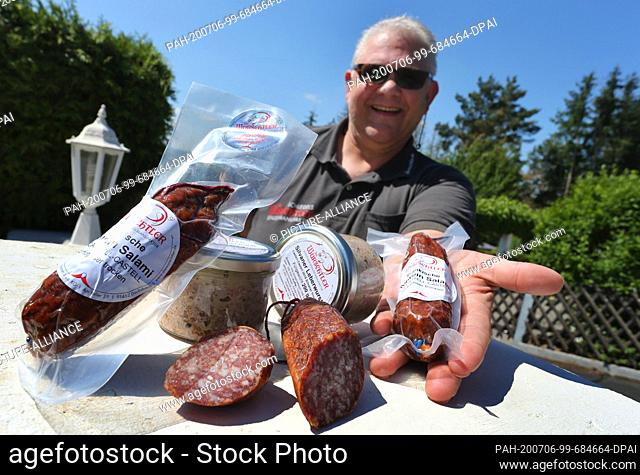 """12 June 2020, Bavaria, Dachsbach: Günther Schlegel, butcher, presents various of his sausage products made with Franconian wine (to dpa: """"""""Sausage"""