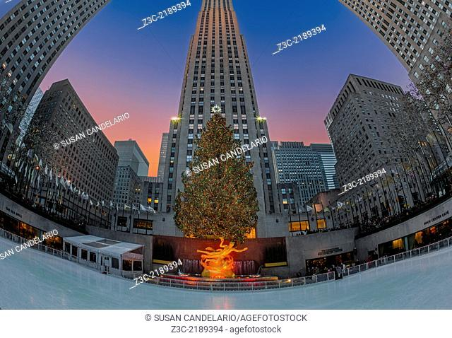 Rockefeller Center's lower plaza with the iconic adorned and illuminated Christmas tree, the ice skating rink along with the bronze sculpture of Prometheus