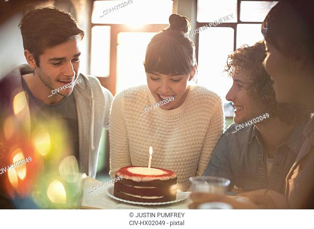 Young adult friends celebrating birthday with cake and candle