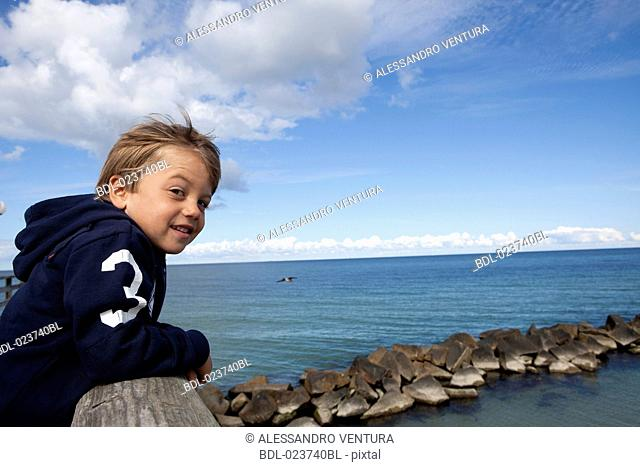 portrait of young boy standing on pier