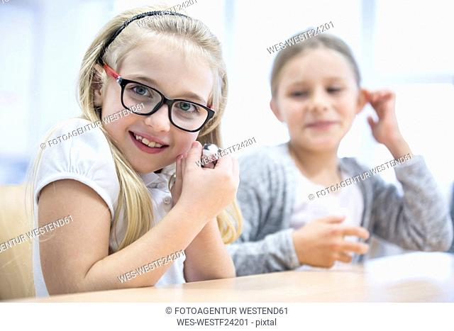 Portrait of smiling schoolgirl in class holding mouse