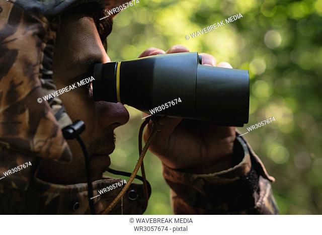 Hunter looking through binoculars in forest