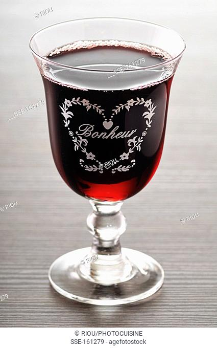 Bonheur engraved on a glass of red wine