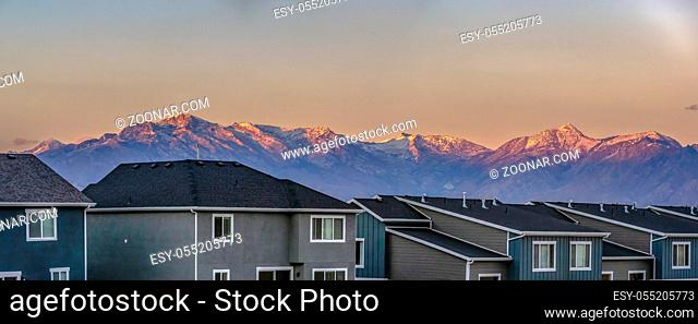 Panorama of homes in front of Timpanogos sunset. Copy space in the sky with pink colors on the tips of Timpanogos mountains with some snow on the very peaks of...