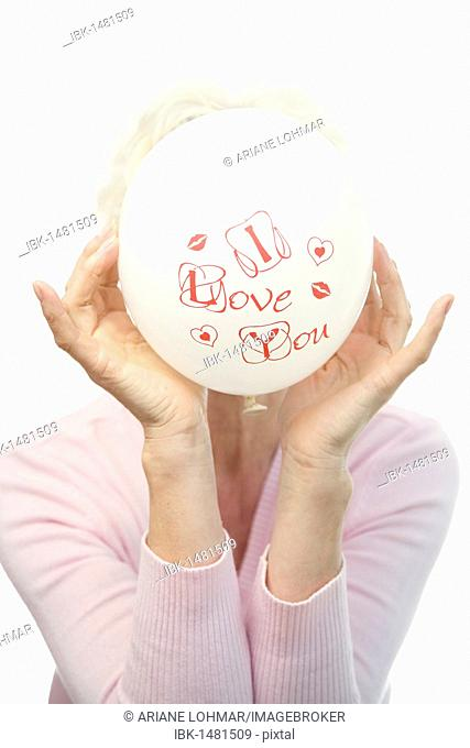 A mature woman holding a white balloon saying I love you, in front of her face