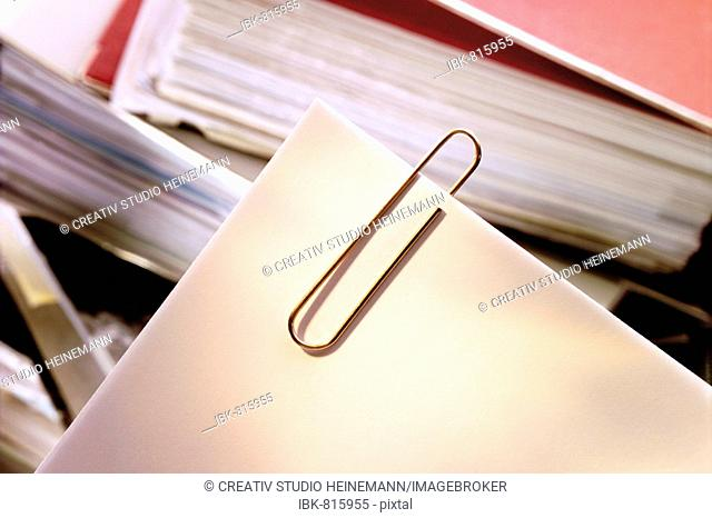 Paperclip, paper clips in front of a stack of files