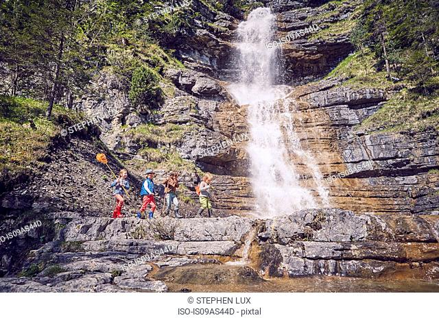 Group of children exploring by waterfall