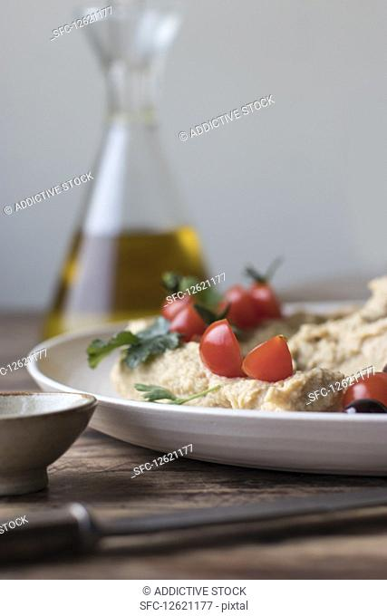 Plate of delicious pesto hummus decorated with cherry tomatoes and beans with parsley