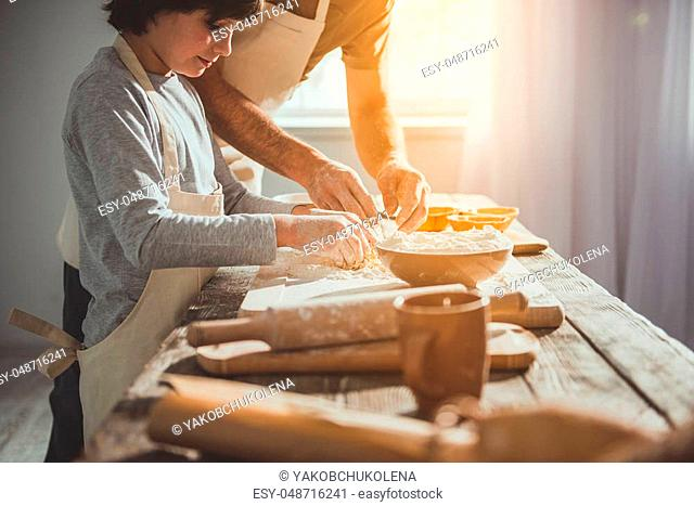 Kid helping his father in the kitchen. They mixing egg and baking powder together