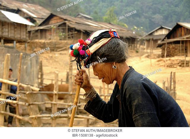 Old woman of the Phoussang ethnic group leaning on a stick and walking in a hunch down way wearing a colourful pompom hat, poverty, village of Ban Phouxang Kaw