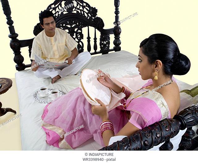 Bengali woman stitching while husband reads the newspaper