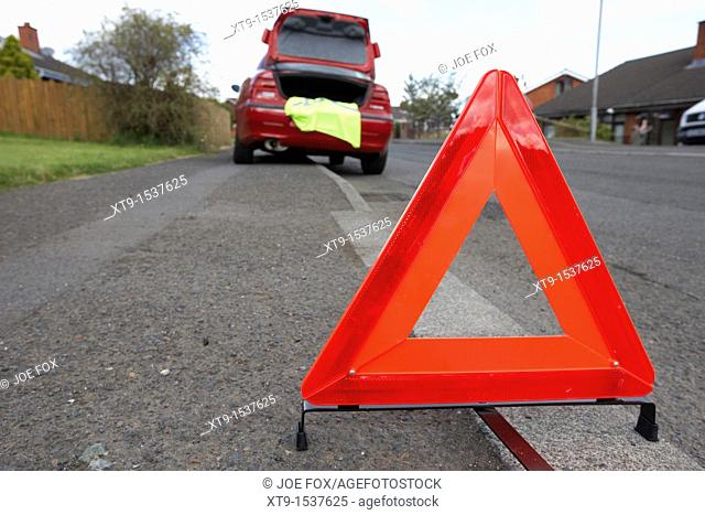 hazard warning triangle laid out on the side of the road in a residential area behind a broken down car