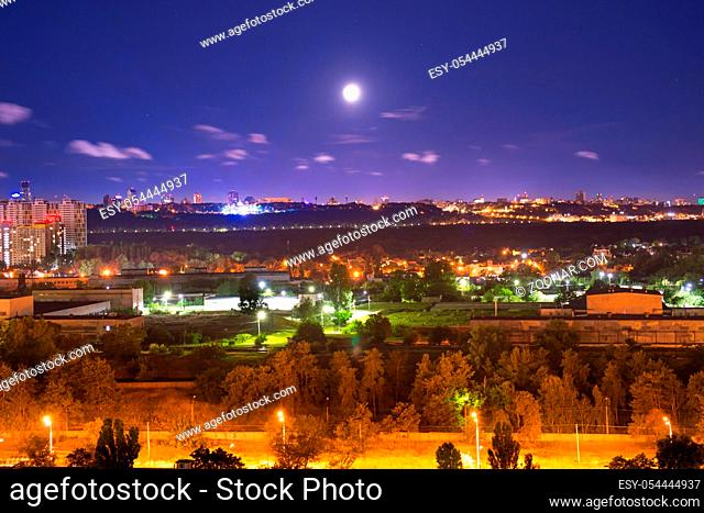 Night city panorama with urban landscape and illuminated buildings under moon and night sky. Kiev