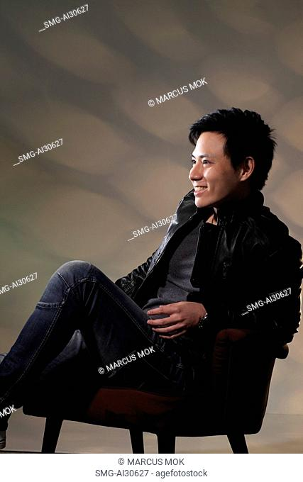 Young man sitting in chair smiling