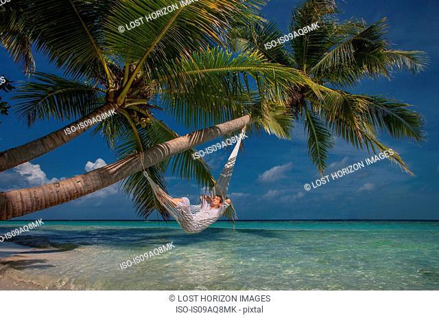 Senior man relaxing in hammock, Maldives