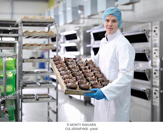 Baker with tray of fresh cakes in cake factory, portrait
