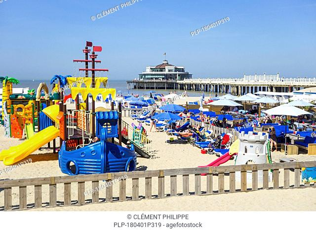 Playground, tourists sunbathing on the beach and the seaside pier at seaside resort Blankenberge along the North Sea coast, West Flanders, Belgium