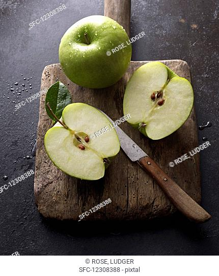Granny Smith apples, whole and halved, on an old wooden board with a knife