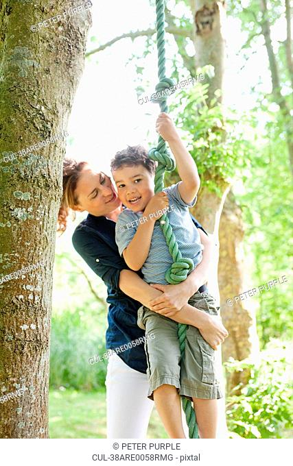 Mother holding son on rope swing